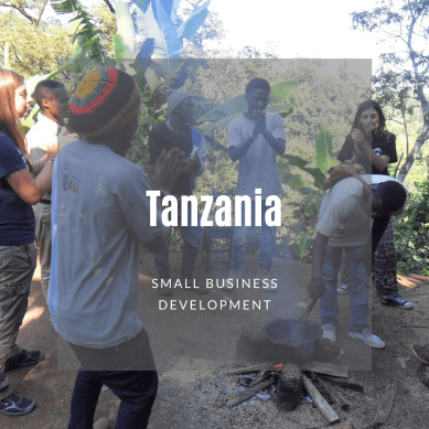 Volunteers and locals in Tanzania around a cooking pot on a fire