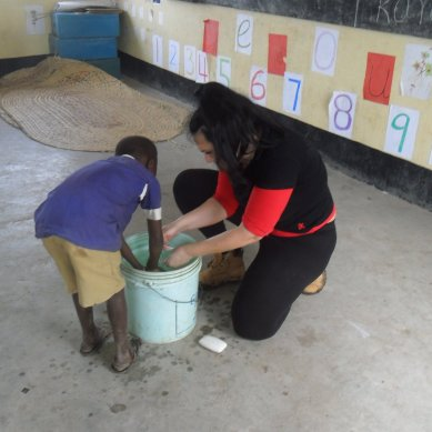 Volunteer helping a boy wash his hands
