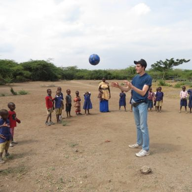 Volunteer playing with a soccer ball with a group of children