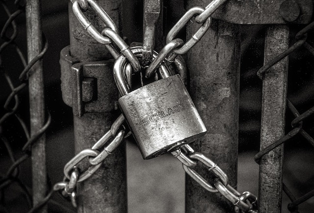 black and white lock on chainlink fence