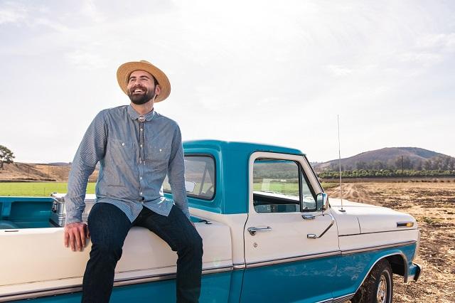 Evan Rochefort of NutraMaize sitting on blue truck bed