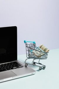 Shopping cart with cash resting on a laptop
