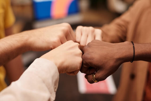 four people doing a fist bump