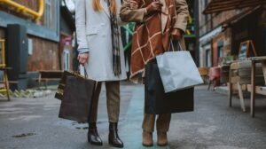 Two people standing on a market street holding shopping bags