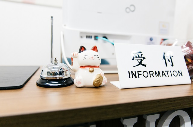 Lucky Cat And Japanese Information Sign On A Computer Desk