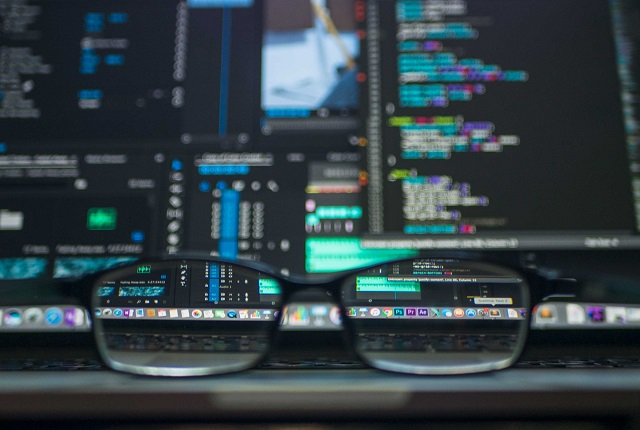 Glasses Resting In Front Of Computer Screen With Code
