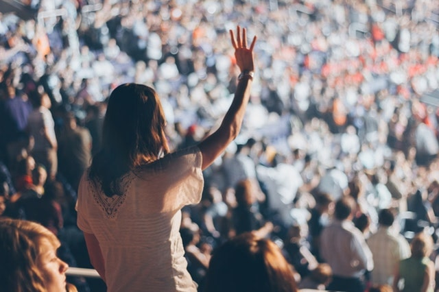 Validate Business Idea Woman Raising Hand In Audience