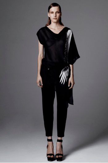 Draped top with white feather design by Helmut Land worn over narrow trousers.