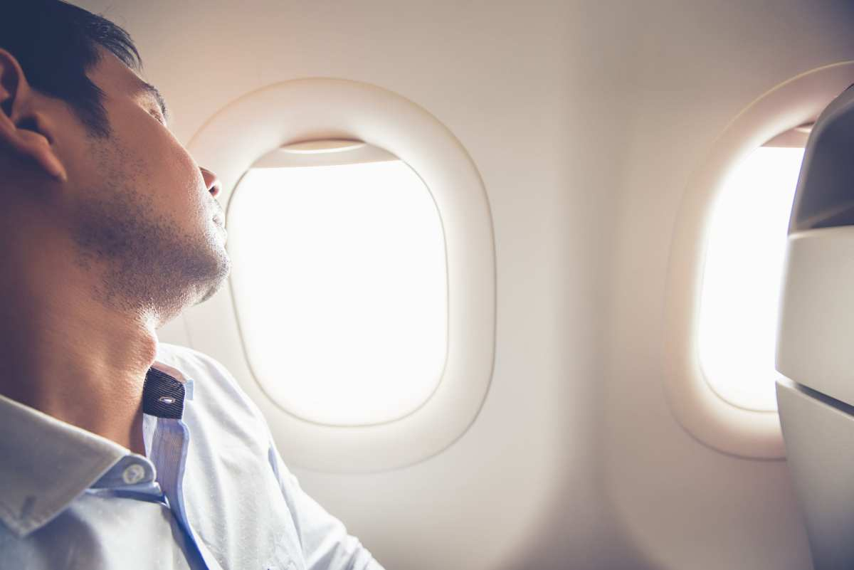 92770239 - tired passenger sleeping on the airplane at window seat