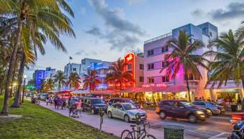 32895695 - miami, usa - aug 23, 2014: people enjoy palm trees and art deco hotels at ocean drive by night. the road is the main thoroughfare through south beach in miami, usa.