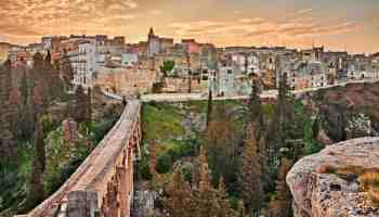 Gravina in Puglia, Bari, Italy: landscape at sunrise of the old town and the ancient aqueduct bridge (viadotto Madonna della Stella) over the deep ravine