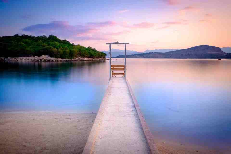 Beautiful Ionian Sea with clear turquoise water, pier with shower and morning summer view from beach (Ksamil, Albania)