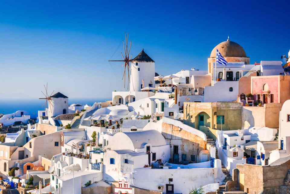 Santorini, Greece. Oia city with white and blue houses in Aegean Sea. Thira, Cyclades Islands.