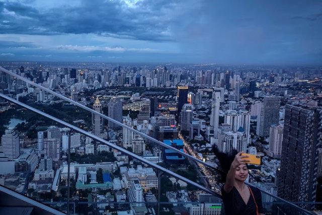 A tourist taking a selfie photograph in front of the city skyline from the Mahanakorn Skywalk's observation deck area.  Image: Vivek Prakash / AFP