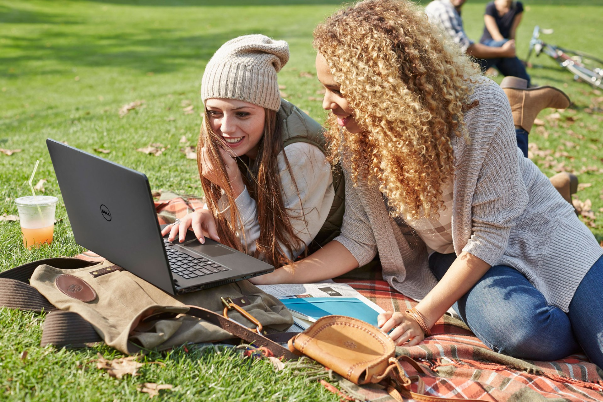 Young Women Sitting in Park Using Inspiron 14 3000 Series Notebo