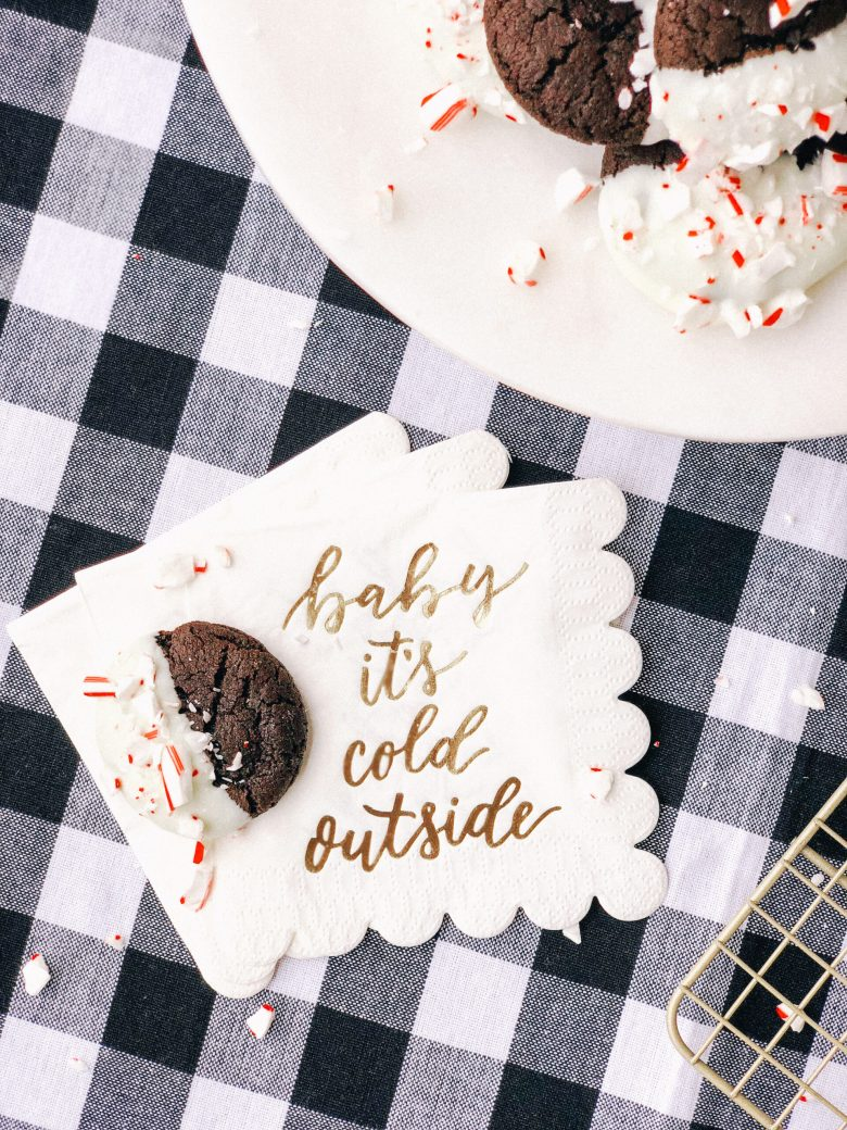 dark chocolate cookies dipped in white chocolate and topped with crushed peppermint on black and white check tablecloth