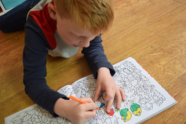 boy colouring in monster colouring book
