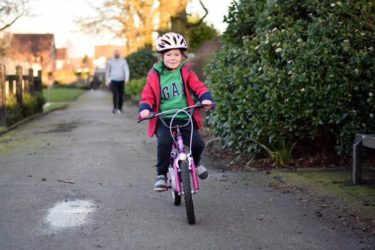 Little girl wearing helmet and riding her bike by herself