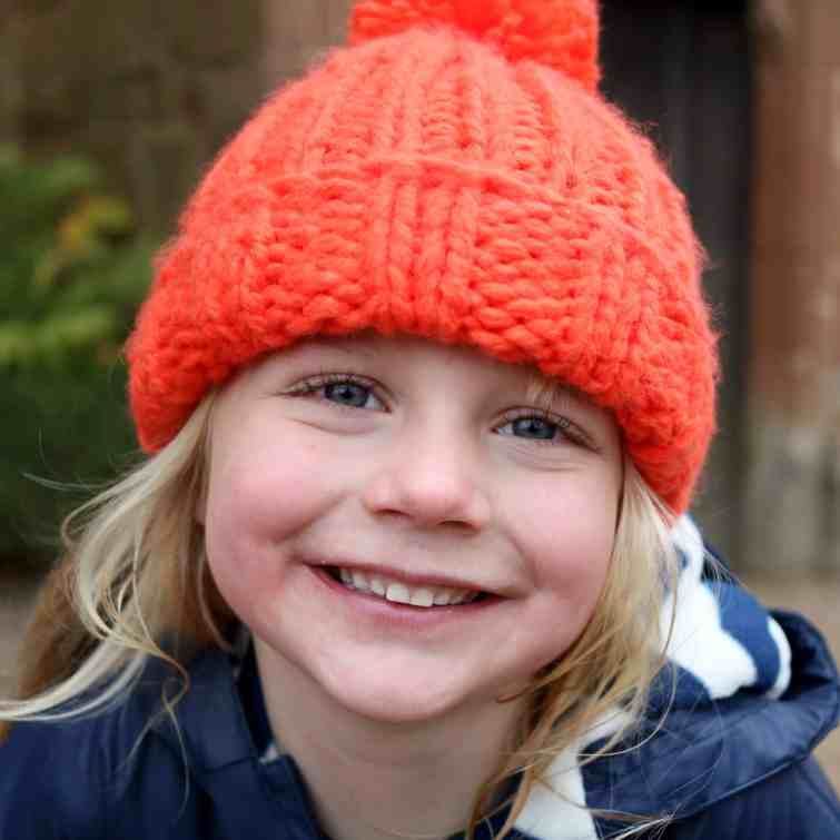 Little girl wearing bright orange hat and smiling broadly