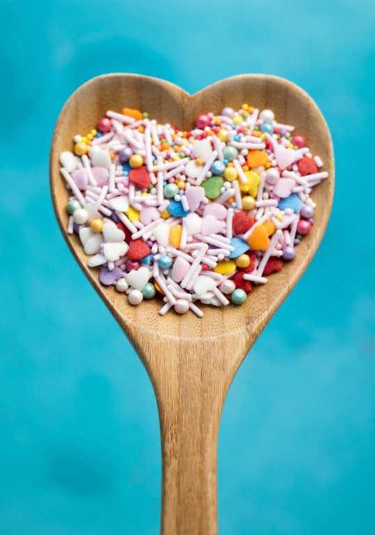 Holzkochlöffel in Herzform mit bunten Zuckerstreuseln darauf