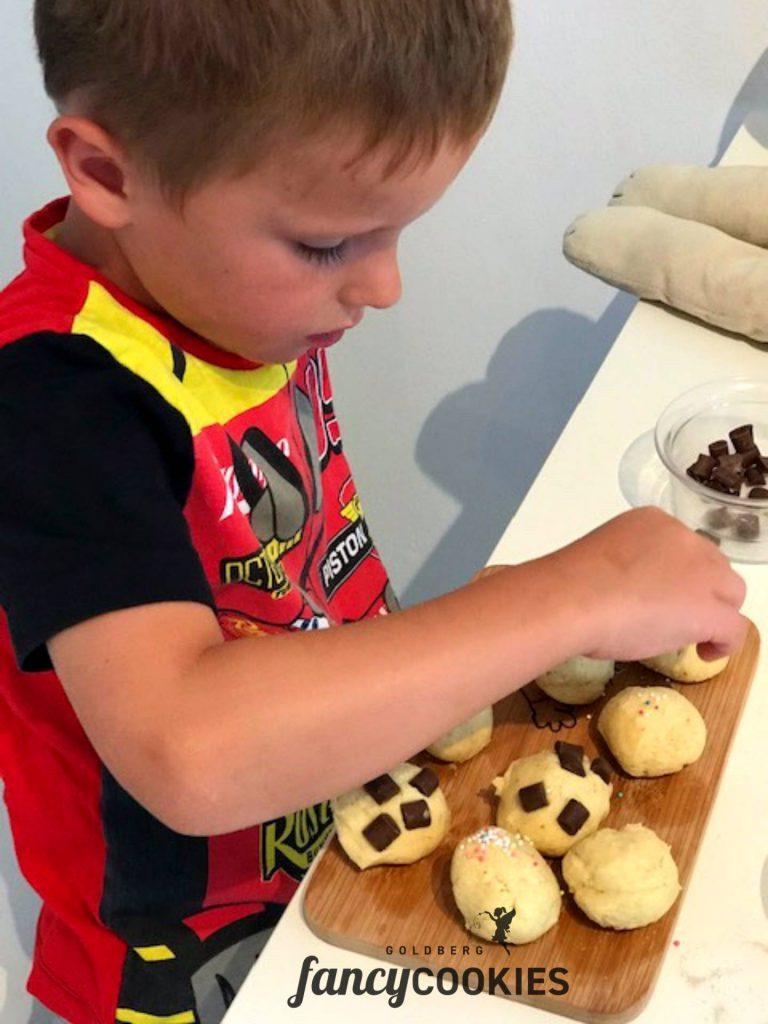 Ein Kind dekoriert Snickerdoodles mit Schokolade.