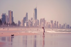 a girl and her dog at the beach with Surfers Paradise in the background