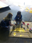 Rory and Mari Hill painting shoes for the Gold Dust Potatoes' Klamath Basin Potato Festival float
