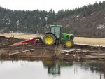 A John Deere tractor pumping water from a canal at the Running Y.