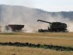 A John Deere tractor pulling a grain cart pulling away from a John Deere combine.
