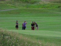 Annie Sproule, Tricia Hill and Maria Contreras watch Katie Walker swing at the Running Y Ranch golf course.