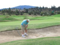 Mike Delisle hitting out of a sand trap at the Running Y Ranch golf course.