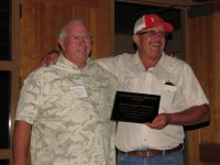 "John Walker giving Duane ""Sarge"" Preston a plaque thanking him for his years of giving Walker Brother advice for growing chipping potatoes."