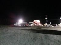 Two spud trucks unload chipping potatoes in the dark at Gold Dust Potato Processors' potato cellars near Malin, OR.