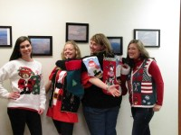 Lexi Crawford, Necia Phillips, Tricia Hill and Trish Briones pose in their Christmas sweaters for the Ugly Sweater Contest.