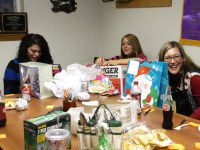 Mayra Martinez, Sarah Mendez and Trish Briones laugh and open gifts at Gold Dust's Office Staff Christmas Party.