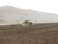 A John Deere tractor pulls a ripper through a field near Gold Dust's campus in Malin, Oregon.