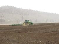 A John Deere tractor pulls a ripper through a field near Gold Dust's campus in Malin, Oregon.