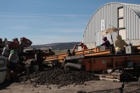 """Walker Brothers workers and equipment separate rocks, """"culls"""" and dirt clods from chipping potatoes at Gold Dust Potatoes' storage facility."""