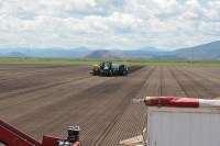A tractor and planter plant chipping potato seed in a field near the Oregon California border north of the Klamath Wildlife Refuge.