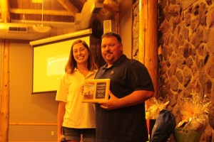 Katie Walker and Billy Conrad of Pape' Machinery with a plaque honoring Pape' Machinery for their support of Make-A-Wish Oregon at Gold Dust's 2018 Open House Field Day dinner.