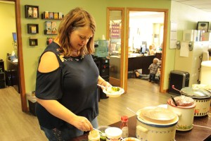 Tricia (Walker) Hill adding broccoli to a potato at Gold Dust Potato Processors' office potato potluck.