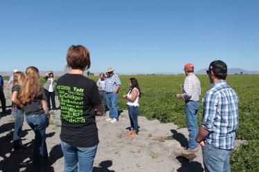 Destiney Huffman talking to group at chipping potato field near Newell, California