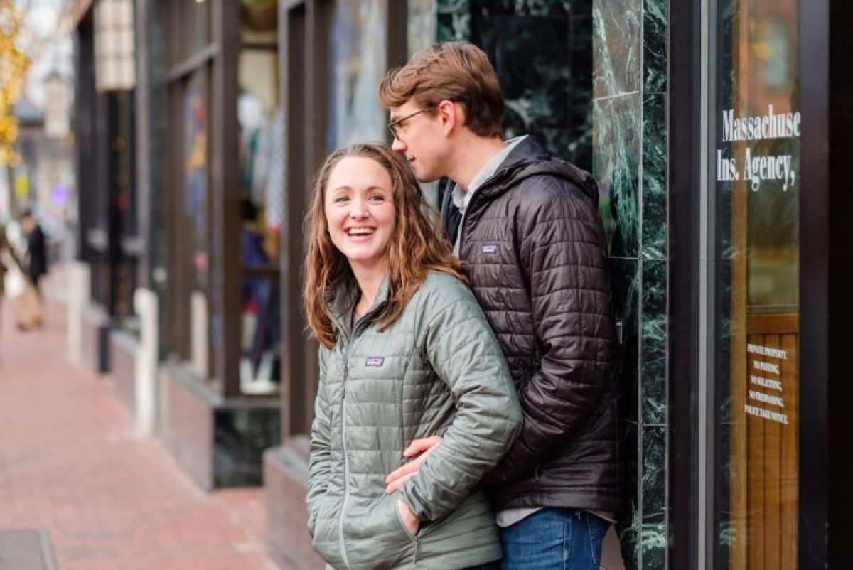Couple hug in front of stores in a winter engagement session in Davis Square
