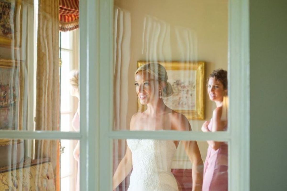 Blonde bride with an updo stands behind a glass window, looking at herself in a mirror as she gets ready for a New England manor wedding