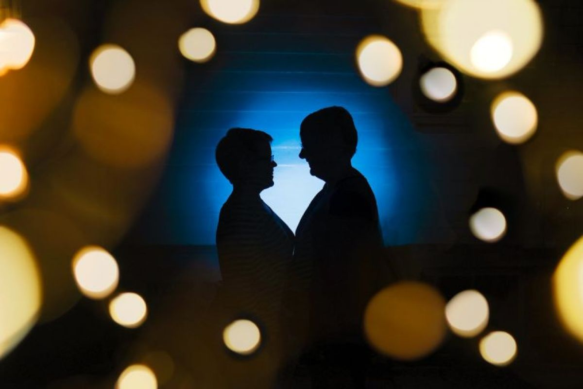 Lesbian couple in a blue halo of light is surrounded by beautiful glowing bokeh balls in artistic edgy wedding portrait