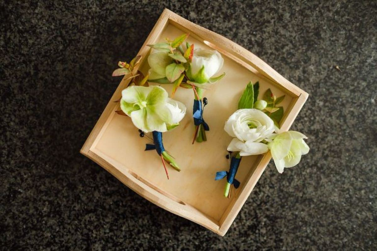 White ranunculus boutonnieres in a wooden box