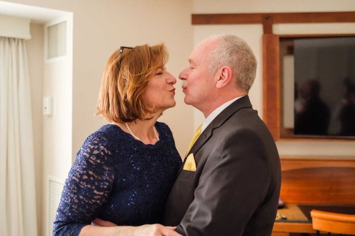 Groom's parents kissing in hotel room