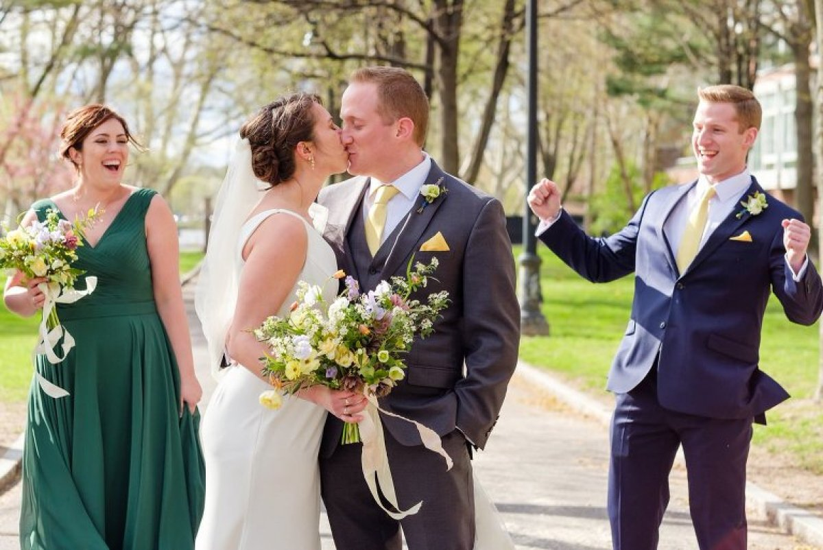 Bride and groom kiss while their wedding team looks on and cheers