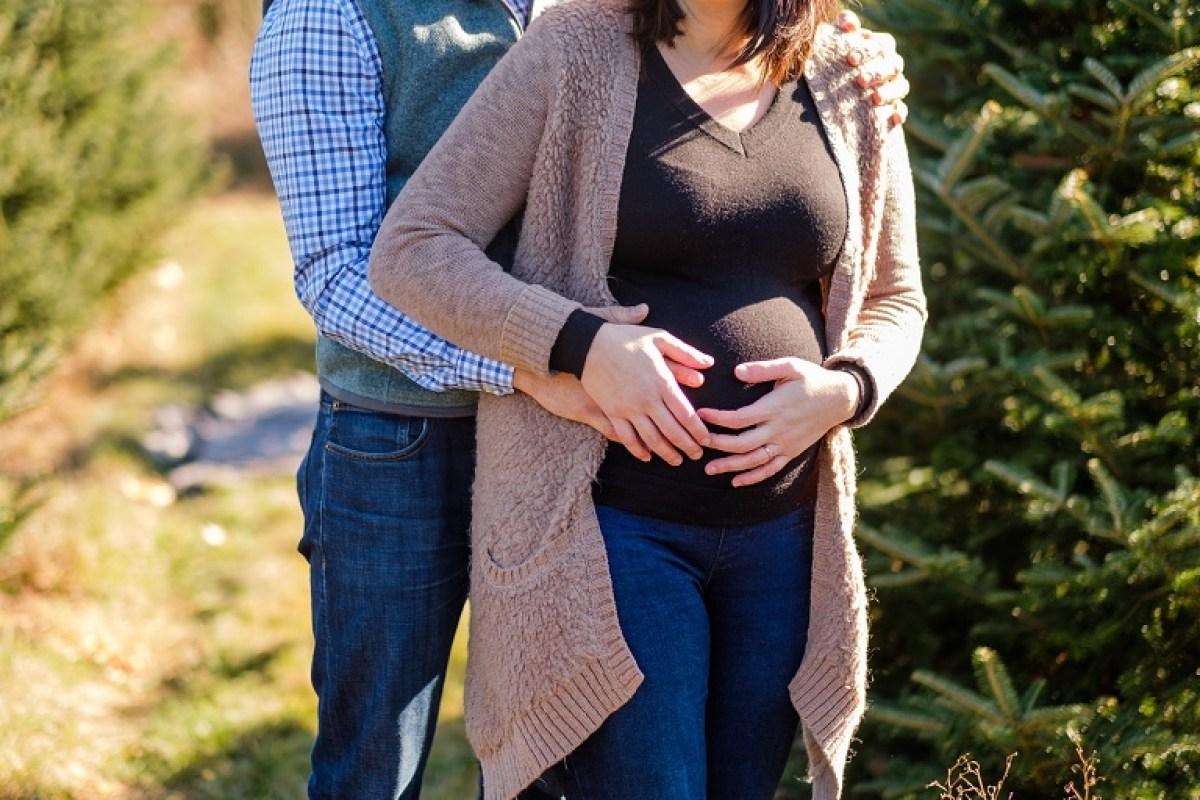 Christmas tree farm maternity photo shoot holding belly