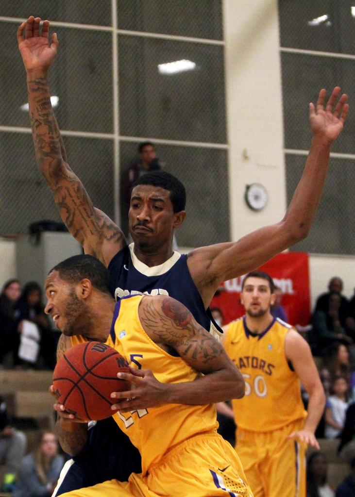 SF State's Brandon Tatum(24) runs into Cal State Monterey Bay's Kris Gallop (15) as he takes the ball to the hoop during a home game against the Otters Saturday, March 1. The Gators won the game 66 to 47. Photo by Gavin McIntyre / Xpress
